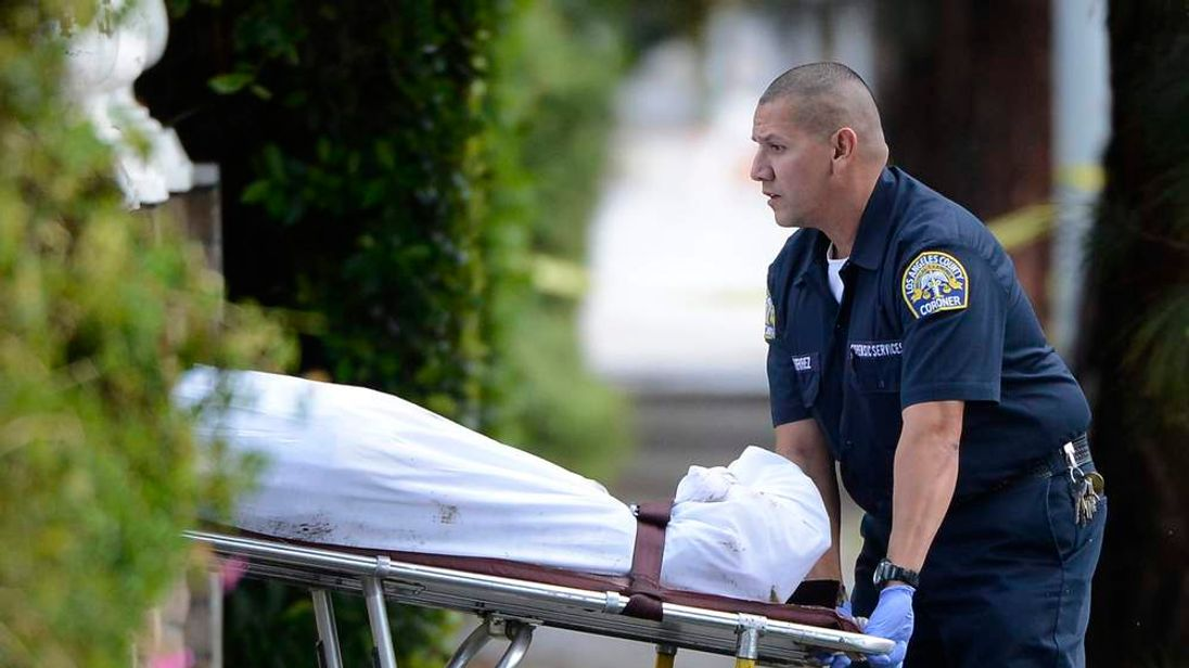 The body of a shooting victim is removed from the crime scene by an official from the Los Angeles Police Department in Northridge, California