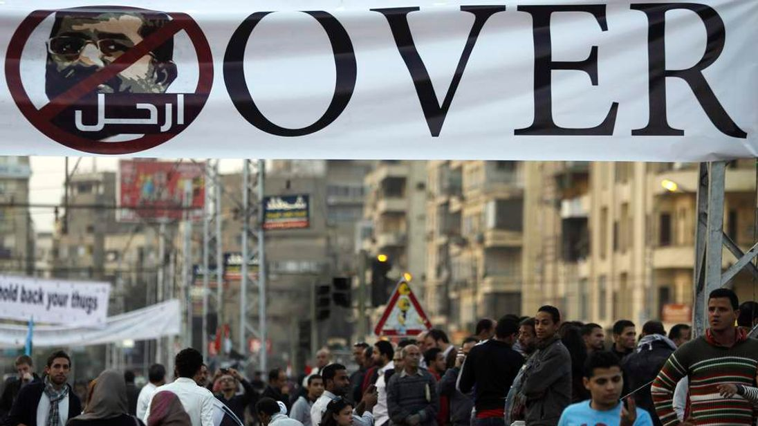 Anti-Mursi protesters stand under a banner in front of the presidential palace in Cairo