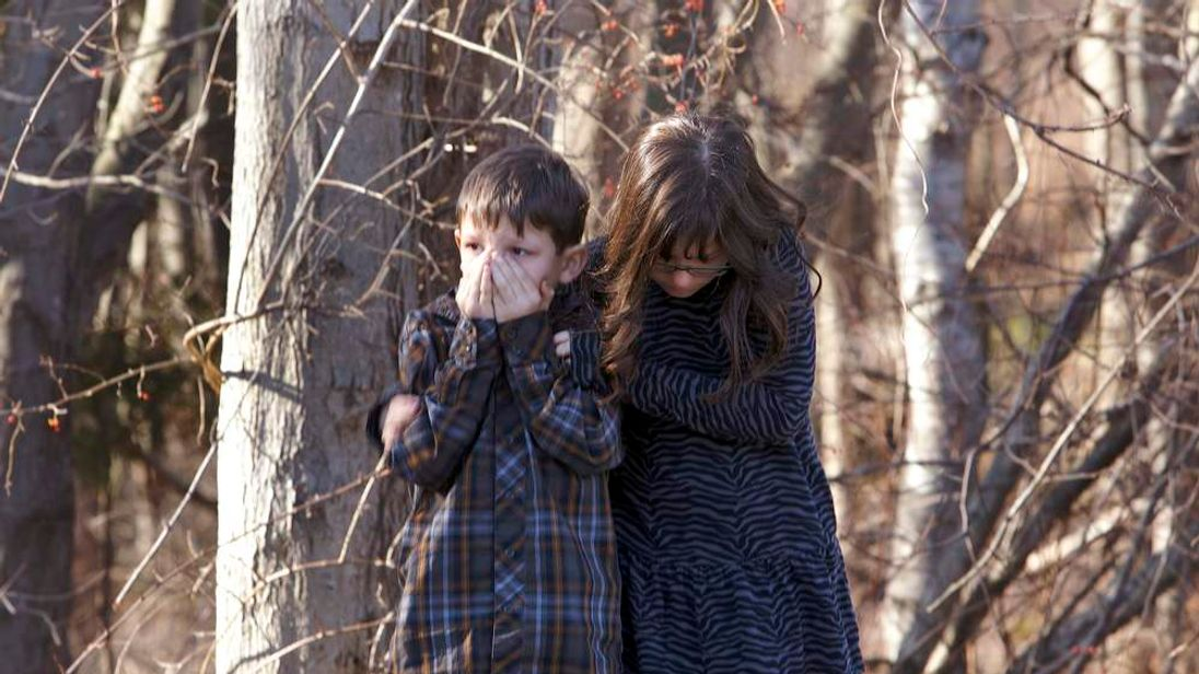 Young children wait outside Sandy Hook Elementary School after a shooting in Newtown