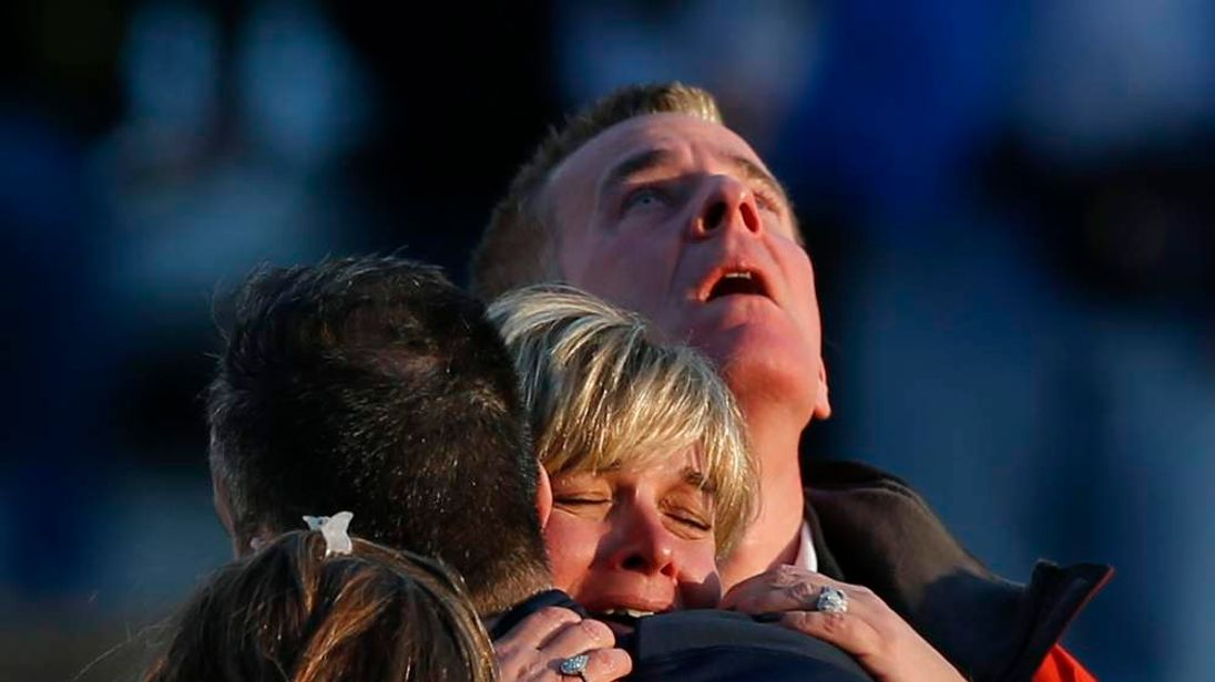 The families of victims grieve near Sandy Hook Elementary School, where a gunman opened fire on school children and staff in Newtown, Connecticut
