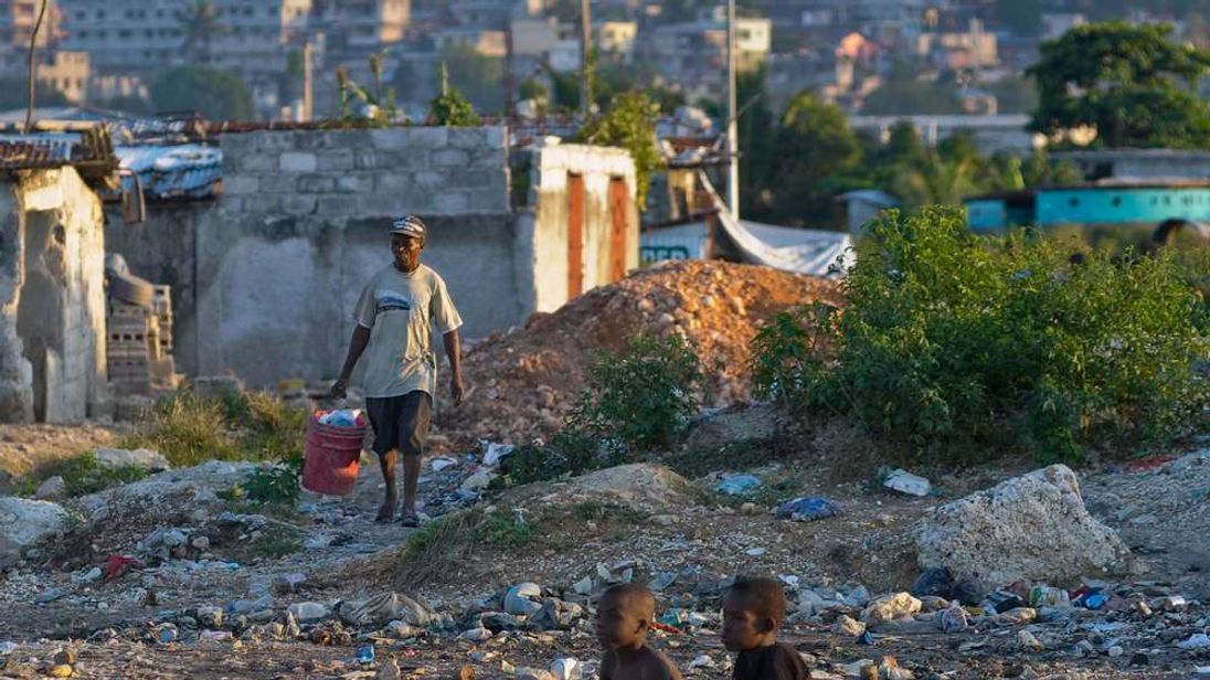 A Haitian carries a bucket filled with waste to be discarded, in a slum area in Port-au-Prince