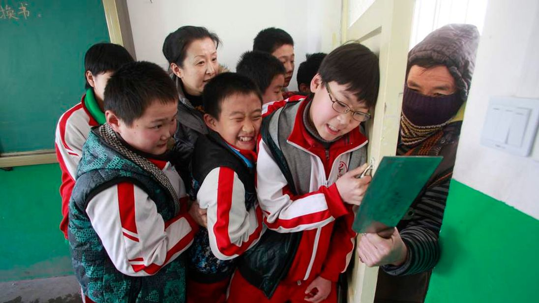A teacher and her students try to shut a door against an intruder during an anti-violence exercise at a primary school in Jinan