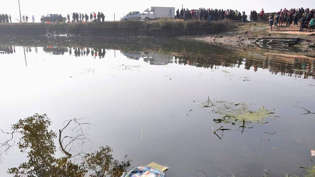 A backpack floats on water after a school van carrying 15 children fell into a pond in Guixi