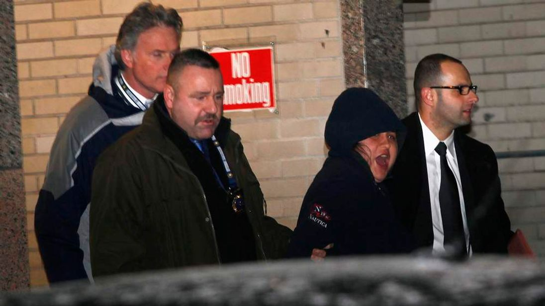 New York City police officers escort Menendez to an awaiting car as she screams, at New York City  Police department 112th Precinct in the Queens Borough of New York