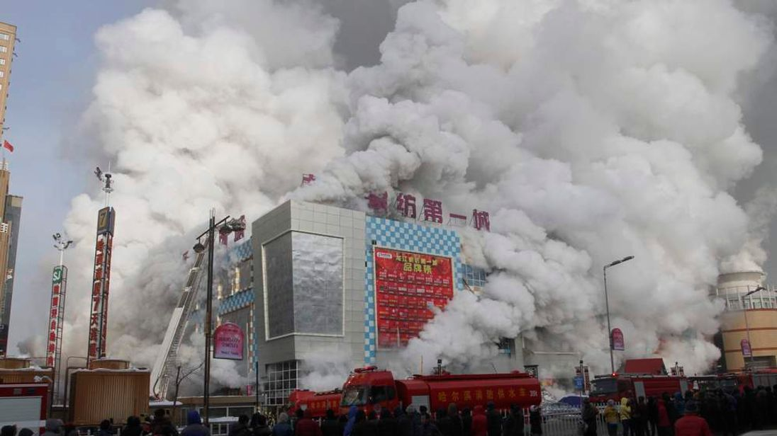 Firefighters try to extinguish a fire at a shopping mall in Harbin, Heilongjiang province