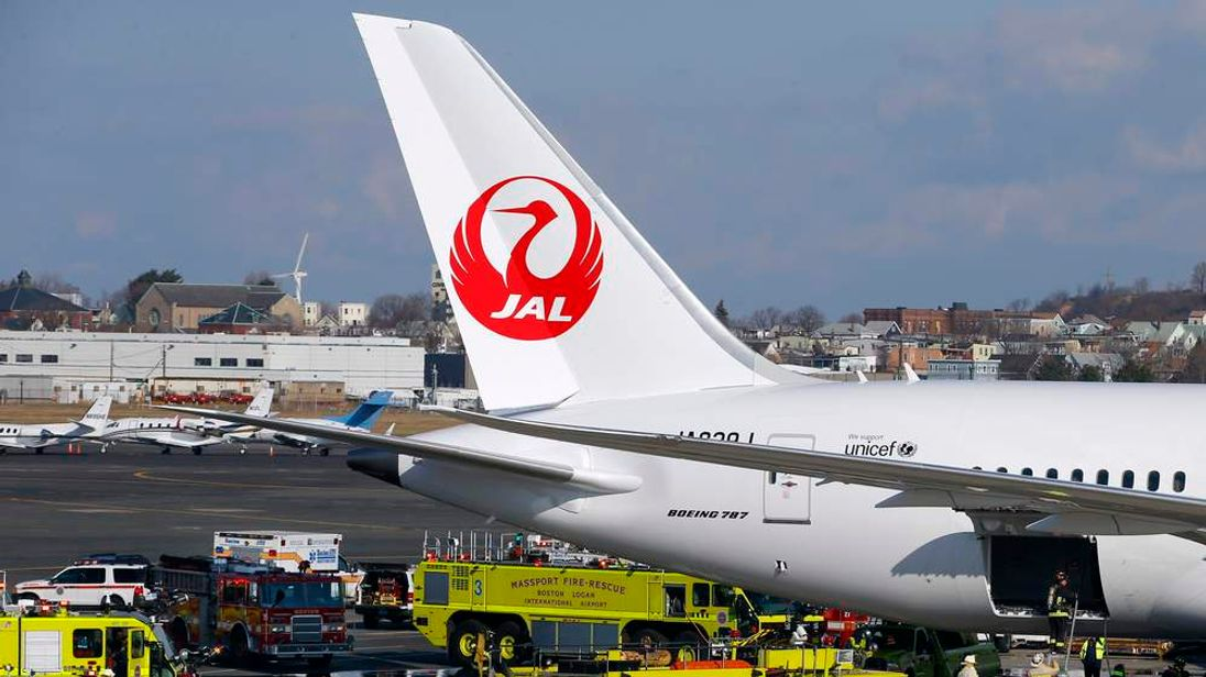 Fire trucks surround Japan Airlines Boeing 787 Dreamliner that caught fire at Logan International Airport in Boston