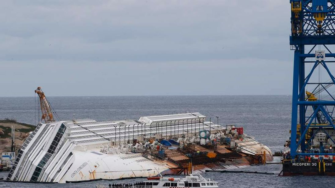 Relatives of victims stand on a ferry in front of the capsized cruise liner Costa Concordia outside Giglio harbour
