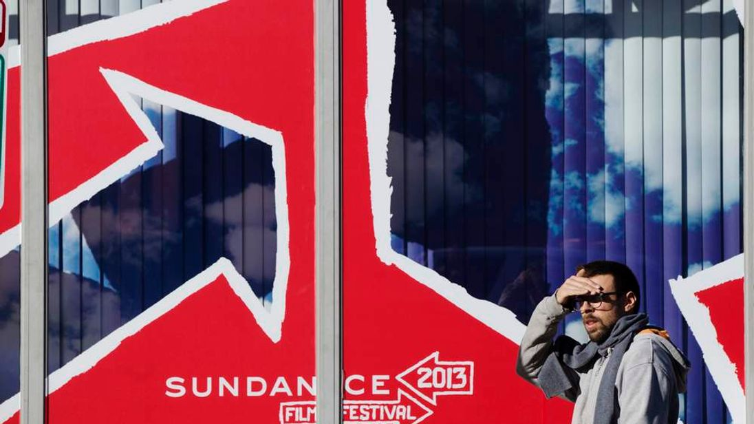 A man shields his eyes from the sun as he walks past a Sundance Film Festival sign on the first day of the festival in Park City, Utah