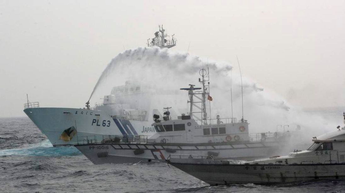 A Japan Coast Guard patrol ship sprays water at a fishing boat that is carrying Taiwanese activists on board while it heads for the disputed islands