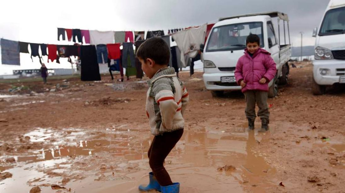 Children play in mud at the Bab Al-Salam refugee camp in Azaz, near the Syrian-Turkish border