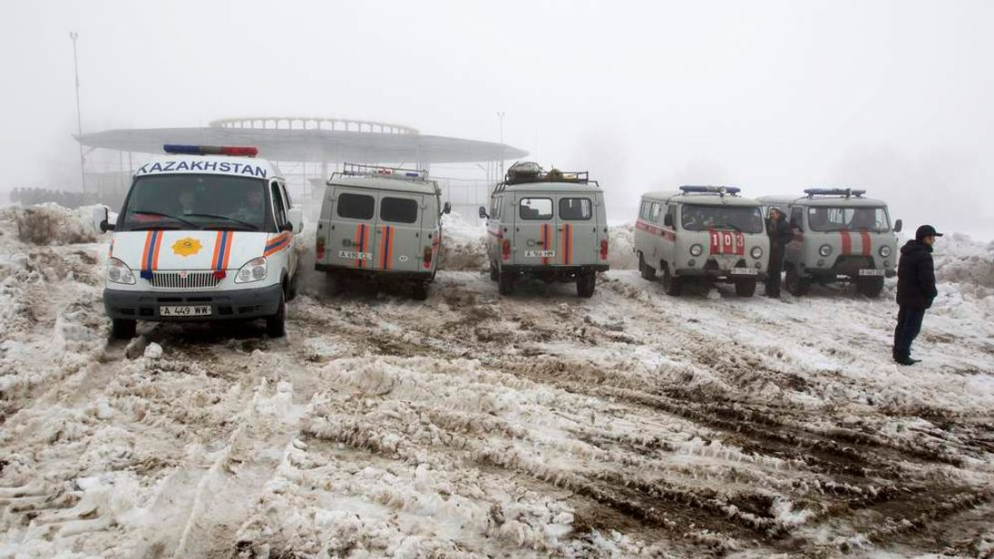 Emergencies Ministry vehicles and ambulances are parked near the site of the plane crash outside Almaty