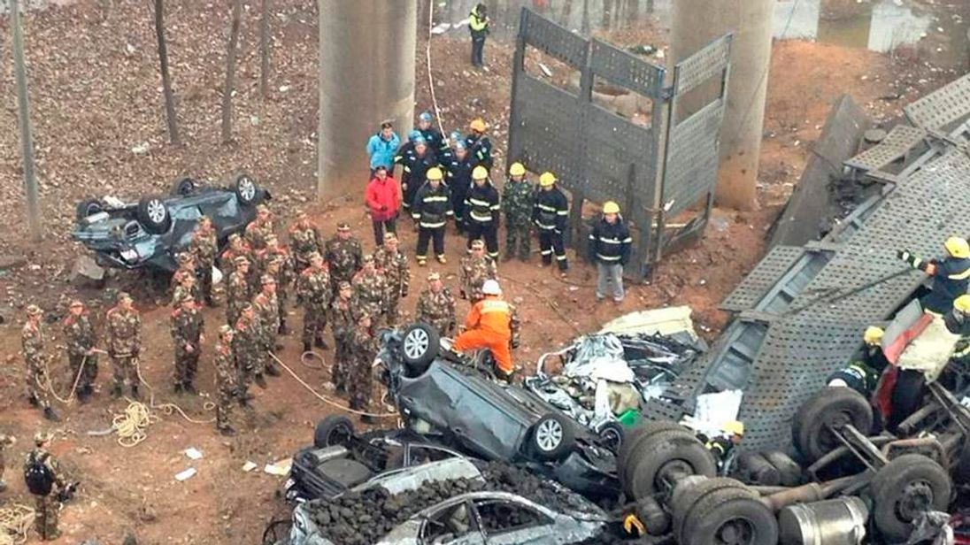Rescuers look for survivors near a wreckage of vehicles after a expressway bridge partially collapsed on the Lianhuo highway in Mianchi county