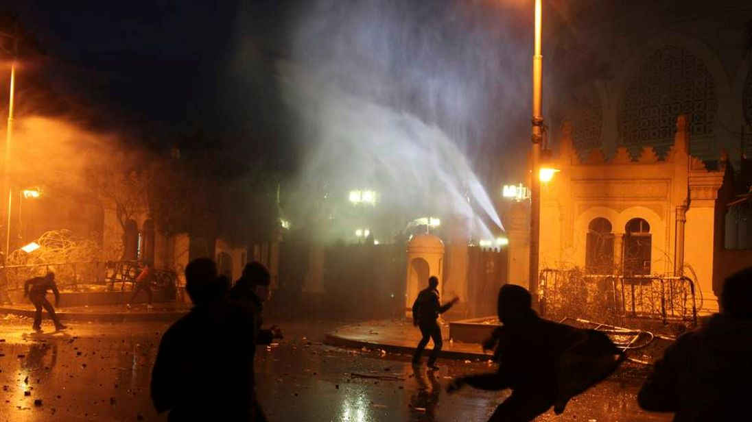 Protesters throw stones at security forces inside the presidential palace during clashes between protesters and police in front of the palace in Cairo