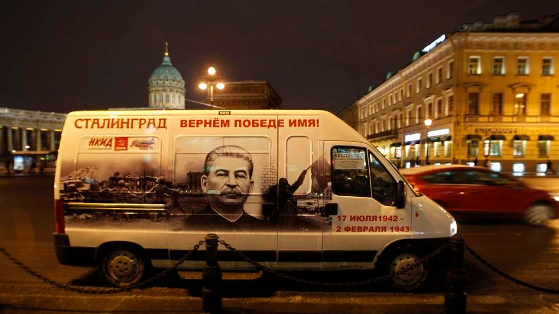 A minibus decorated with a portrait of Soviet dictator Josef Stalin drives in front of the Kazan Cathedral in St. Petersburg