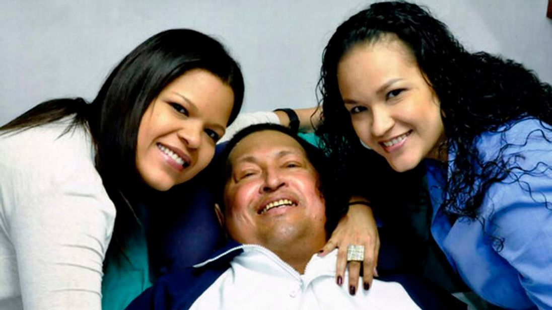 Venezuela's President Hugo Chavez smiles in between his daughters while recovering from cancer surgery in Havana