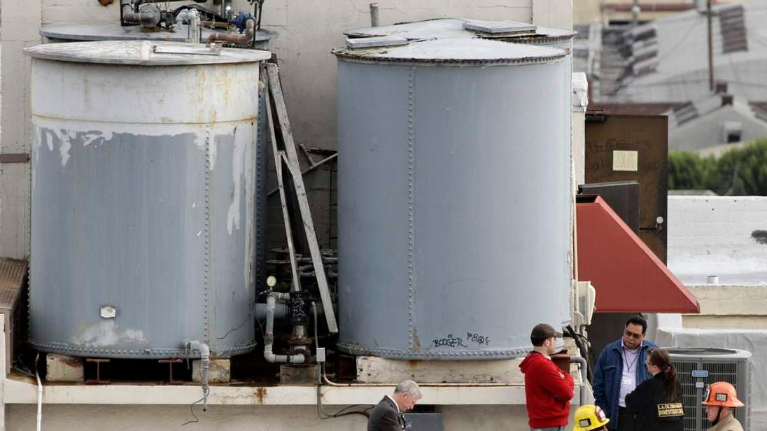 Authorities stand on the rooftop of Cecil Hotel after a body was found in a water tank in Los Angeles