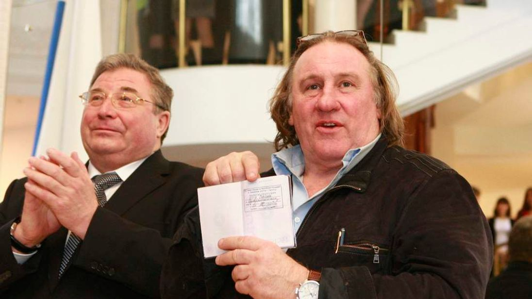 French film star Depardieu shows his passport as Volkov, head of the Republic of Mordovia, applauds during a visit to the town of Saransk