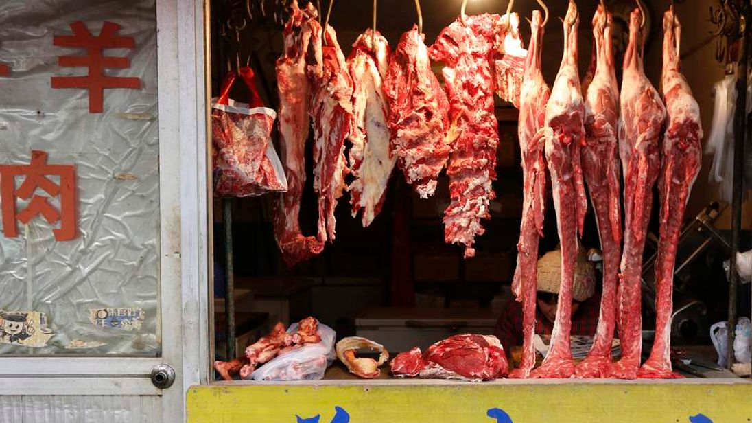 A vendor reads as she waits for customers inside a butcher shop at a market in Beijing