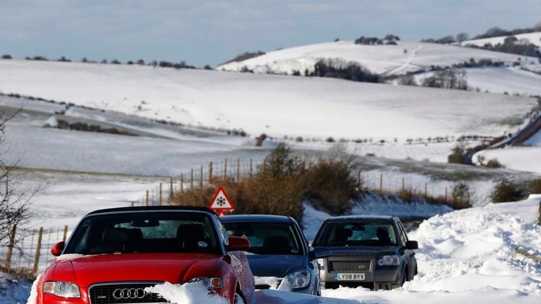 Cars remain stuck in snow on the South Downs near Brighton in southern England