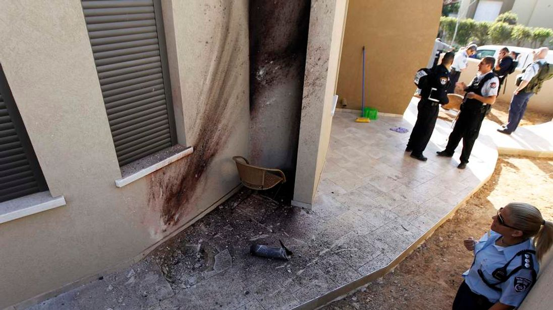 An Israeli policewoman looks at the damage after a rocket landed in Sderot