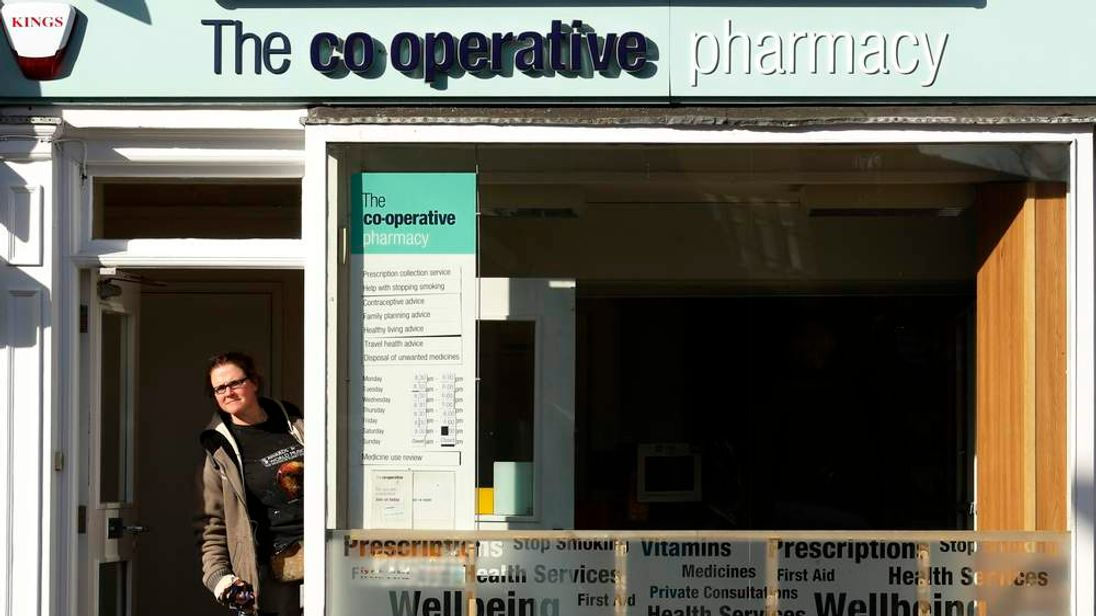 A customer looks out the door of a Co-operative Pharmacy in Brighton in southern England