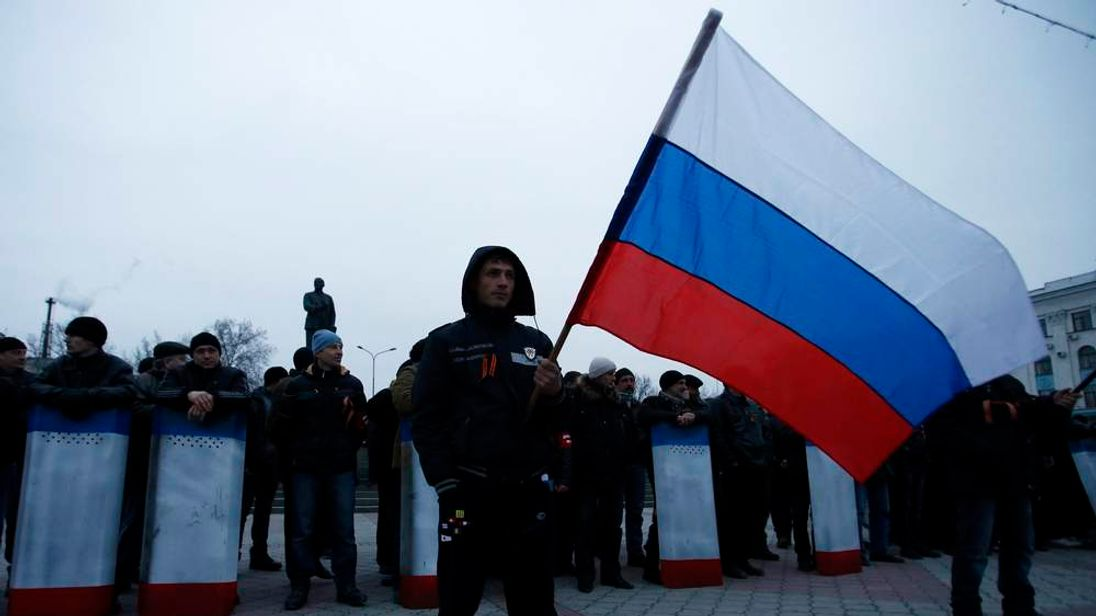 A man holds the Russian flag during a pro-Russian rally in Simferopol, Crimea