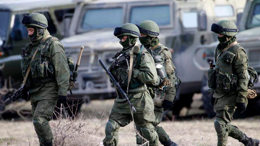 Uniformed men walk near a Ukrainian military base in the village of Perevalnoye