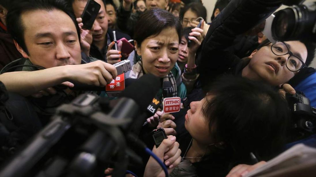 A woman, whose husband is a passenger of Malaysia Airlines flight MH370, complains about Malaysia Airlines to journalists as she attempts to leave a hotel in Beijing