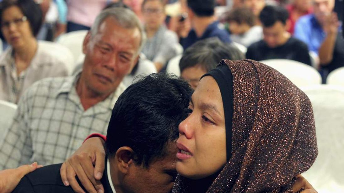 Family members of those onboard the missing Malaysia Airlines flight MH370 cry at a hotel in Putrajaya