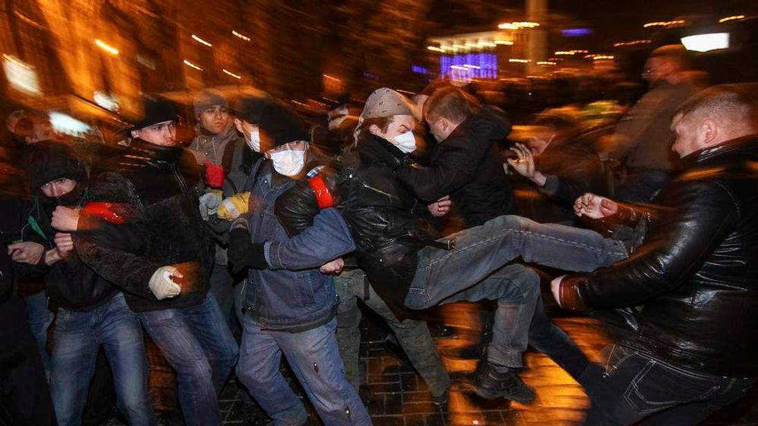 Participants of an anti-war rally (L) clash with a pro-Russian supporter during their respective rallies in Donetsk