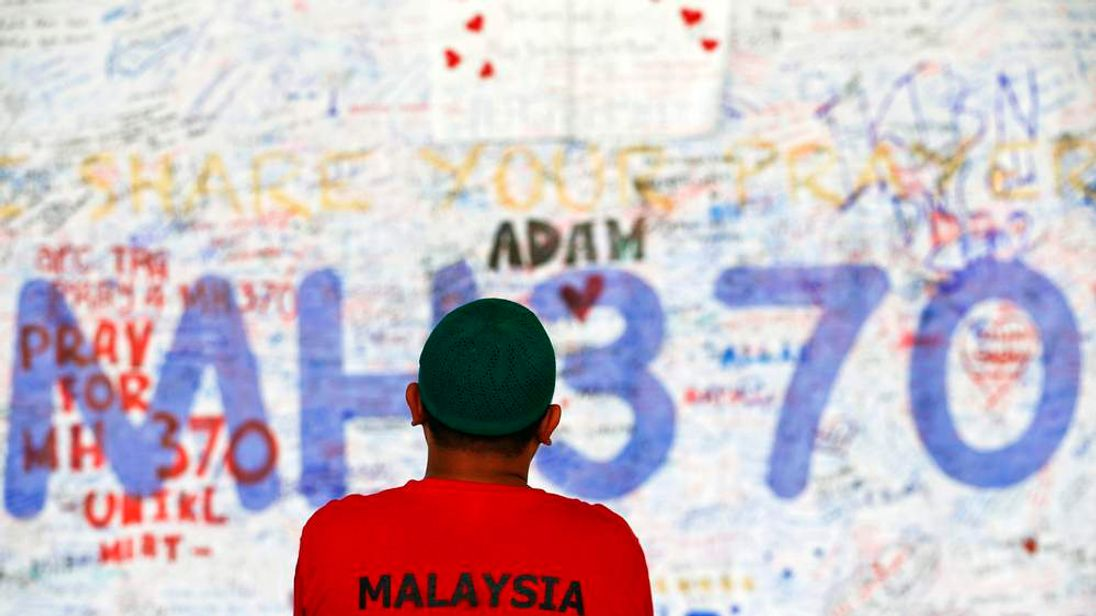 A man stands in front of a board with messages of hope and support for the passengers of the missing Malaysia Airlines MH370 at the departure hall of the Kuala Lumpur airport