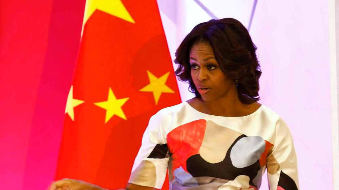 U.S. first lady Michelle Obama gestures in front of a Chinese national flag after giving a speech at the Peking University in Beijing