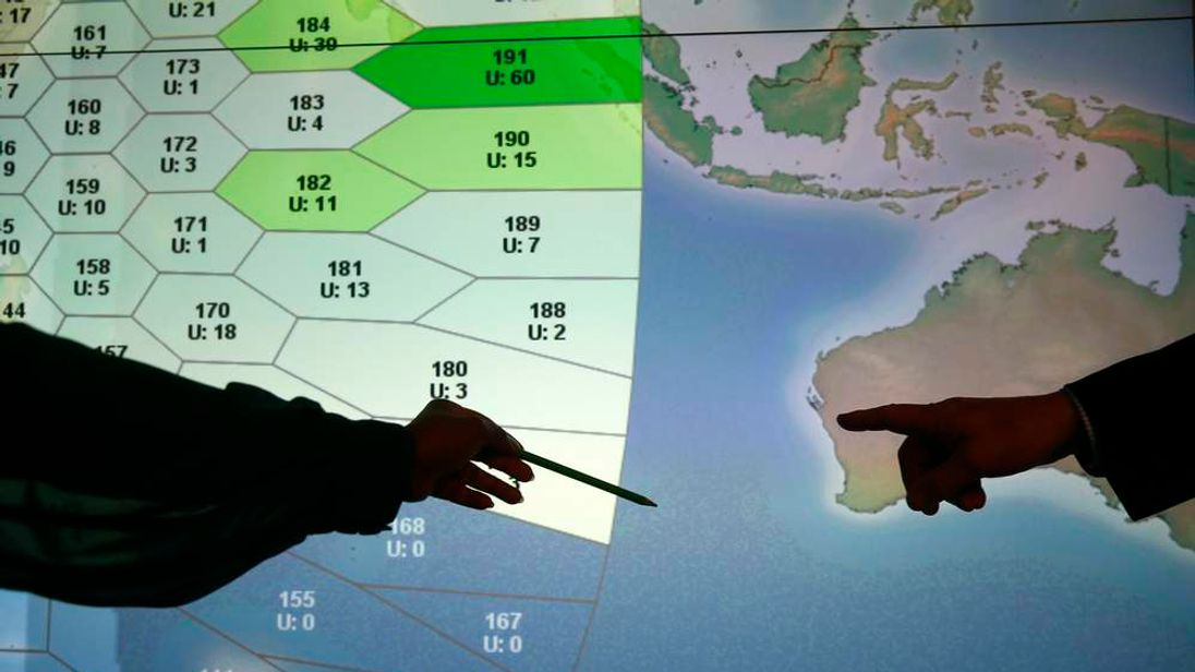 Member of staff at satellite communications company Inmarsat point to a section of the screen showing the southern Indian Ocean to the west of Australia, at their headquarters in London
