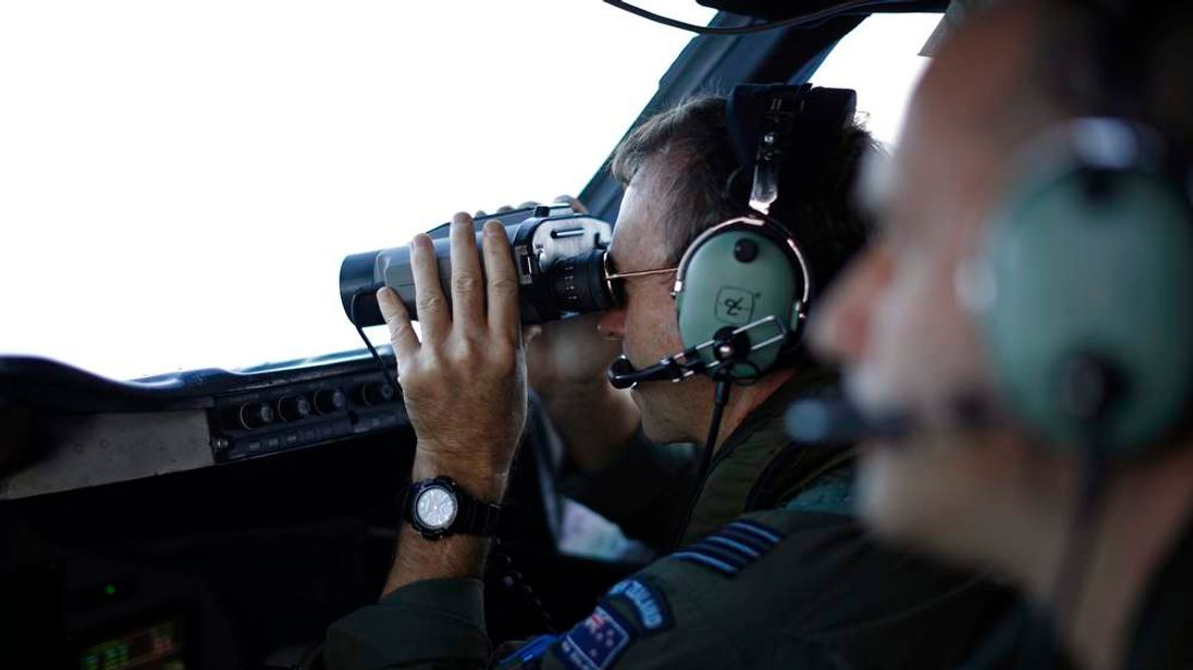 Wing Commander Shearer looks through binoculars on a Royal New Zealand Air Force P-3K2 Orion aircraft during a search for the missing Malaysian Airlines MH370 over the southern Indian Ocean