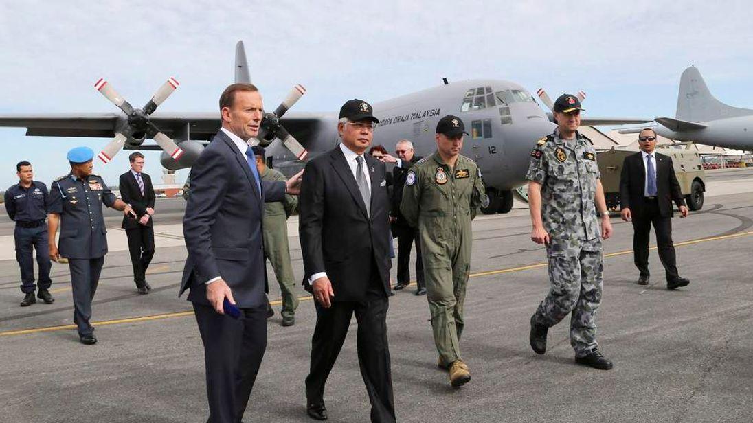 Australia's Prime Minister Tony Abbott and Malaysia's Prime Minister Najib Razak tour the tarmac of RAAF Base Pearce near Perth