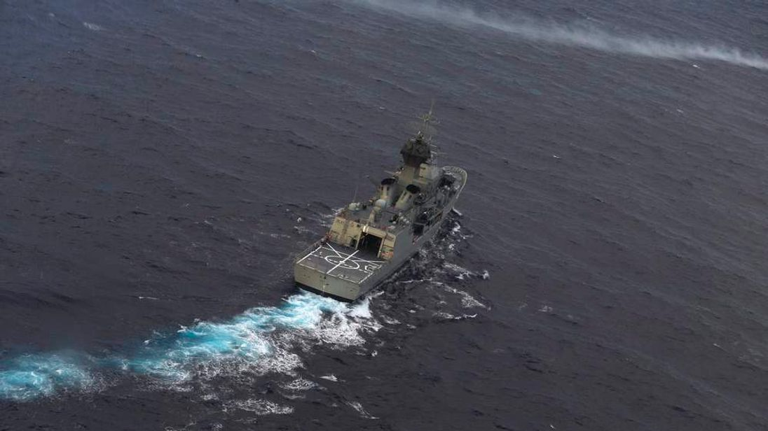RAN ship HMAS Perth is guided into position by a RNZAF P-3K2 Orion aircraft to recover an object in the southern Indian Ocean, as the search continues for missing flight MH370.