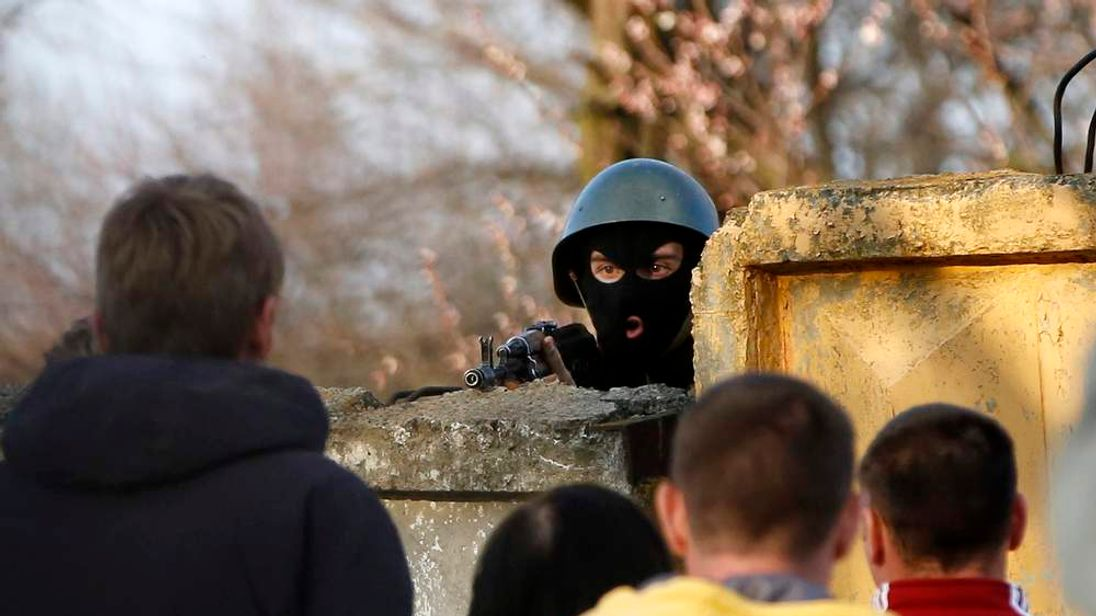 An Ukrainian soldier aims his rifle at pro-Russia protesters gathered in front of a Ukrainian airbase in Kramatorsk
