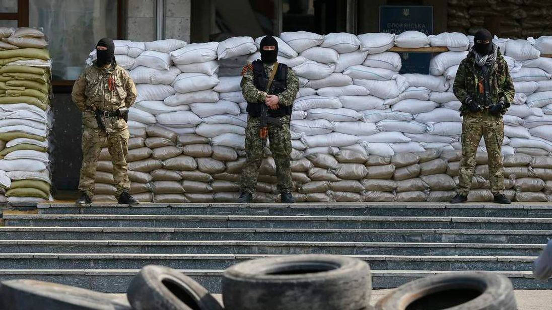 Armed men stand guard in front of barricades outside the mayor's office in Slaviansk