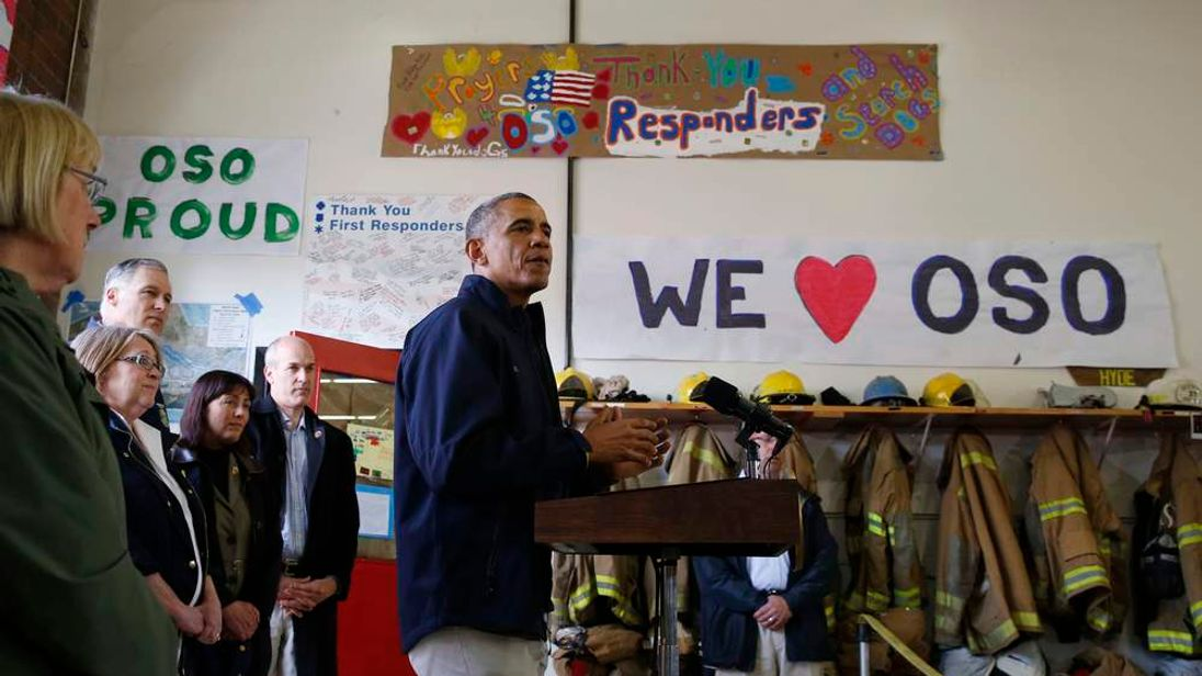 U.S. President Barack Obama talks to first responders after touring the mud slide damage in Oso, Washington
