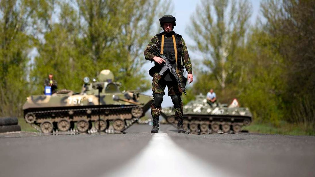 A Ukrainian soldier stands guard in front of armoured personnel carriers at a check point near the village of Malinivka