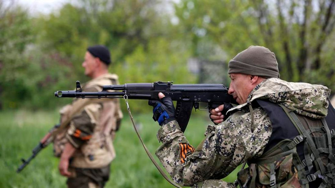A pro-Russian rebel aims his rifle at a checkpoint near a Ukrainian airbase in Kramatorsk