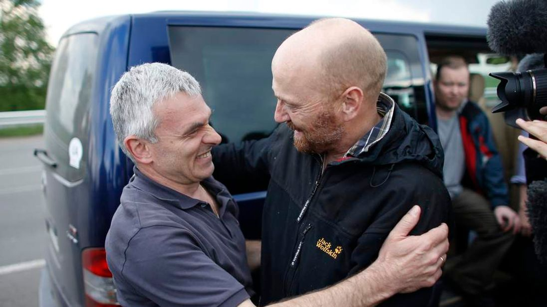 OSCE observer Axel Schneider hugs a colleague on a road 30 km (19 miles) from Donetsk after being freed by pro-Russian separatists