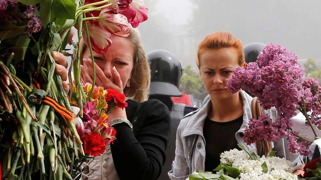 Women bring flowers in memory of people killed in recent street battles