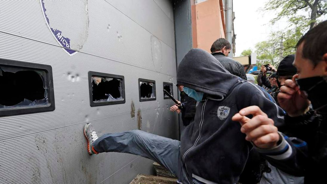 Participants of a rally attack a city police department as they demand the release of people arrested after recent street battles between pro-Russian and pro-Ukrainian supporters in the Black Sea port of Odessa