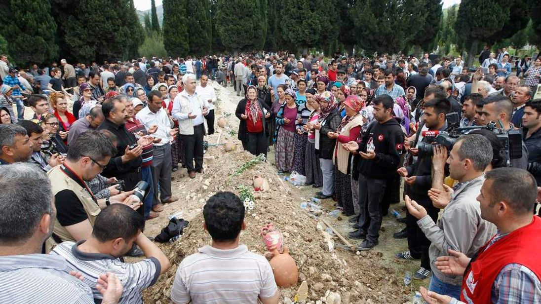 People mourn at the grave of a dead miner after the burial service in a cemetery in Soma, a district in Turkey's western province of Manisa