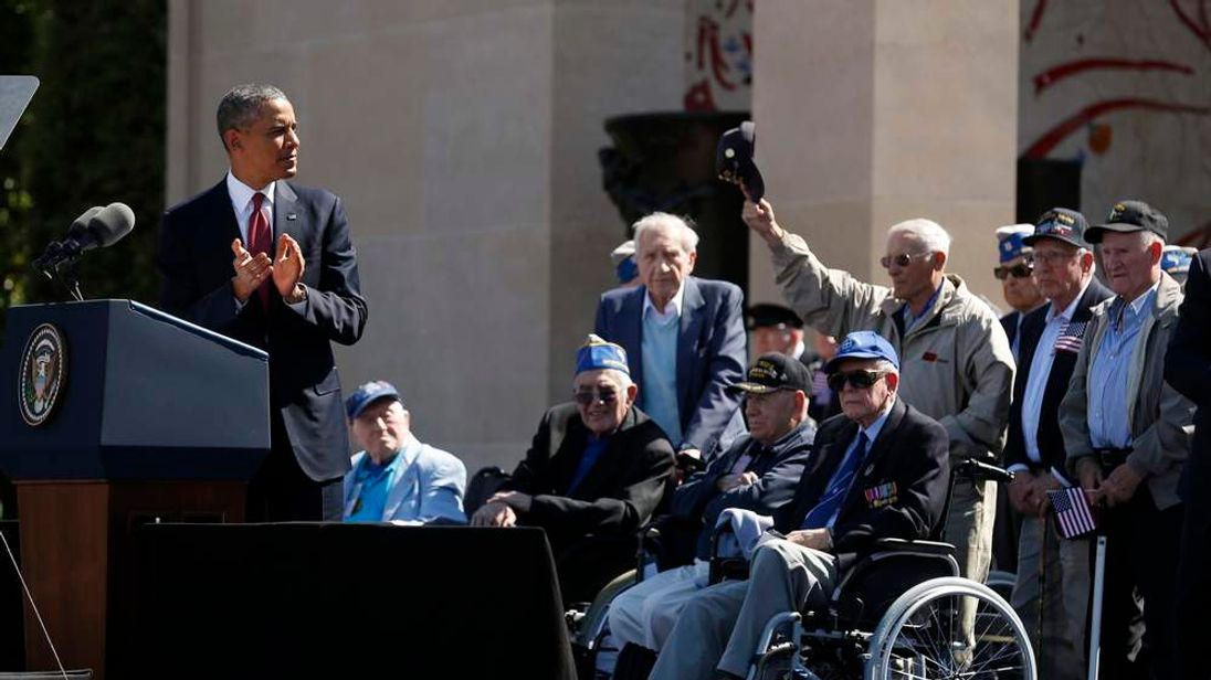 A veteran stands and holds out his hat as U.S. President Barack Obama applauds in Colleville-sur-Mer