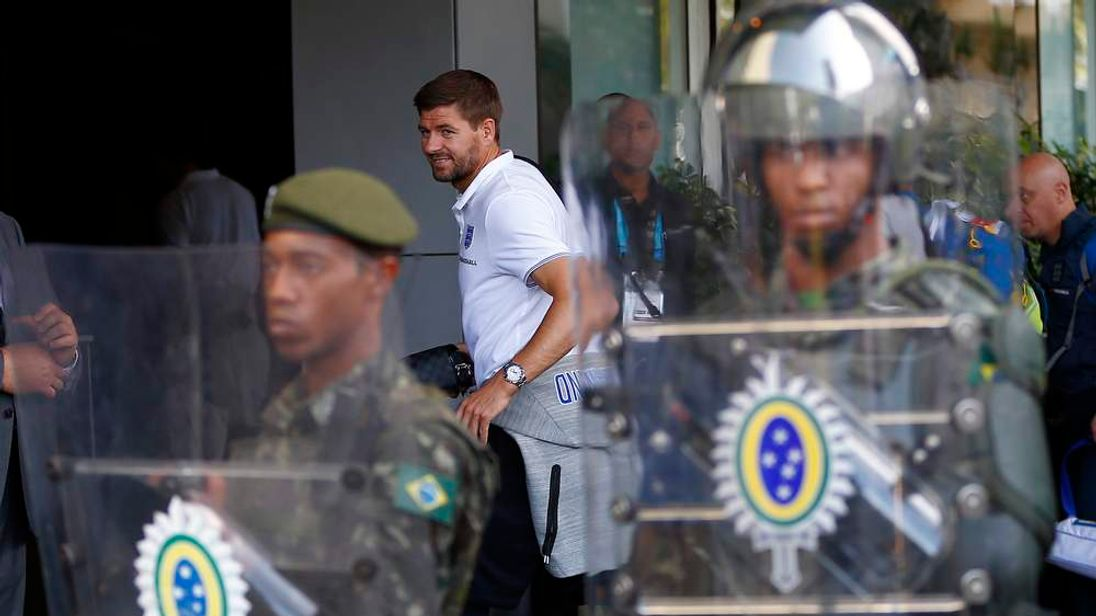 England's Gerrard walks past Brazilian army personnel