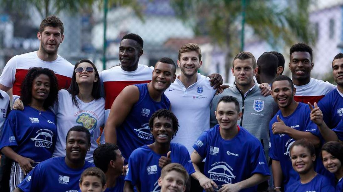 England soccer players pose with Brazilian dancers a visit to sports complex at the Rocinha slum in Rio de Janeiro