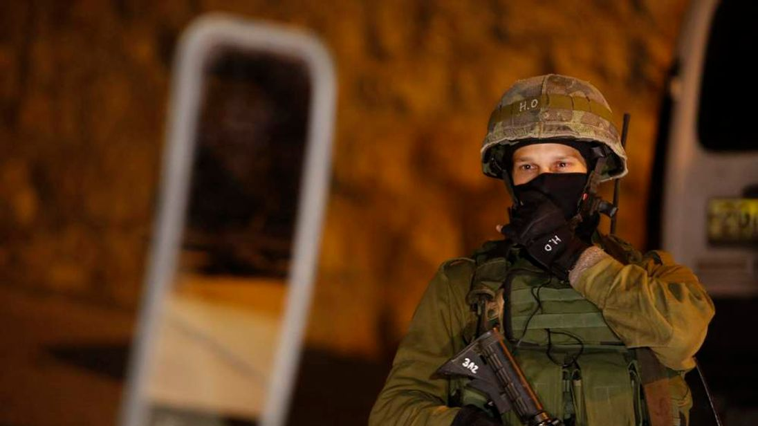 An Israeli soldier stands guard in the West Bank city of Hebron.
