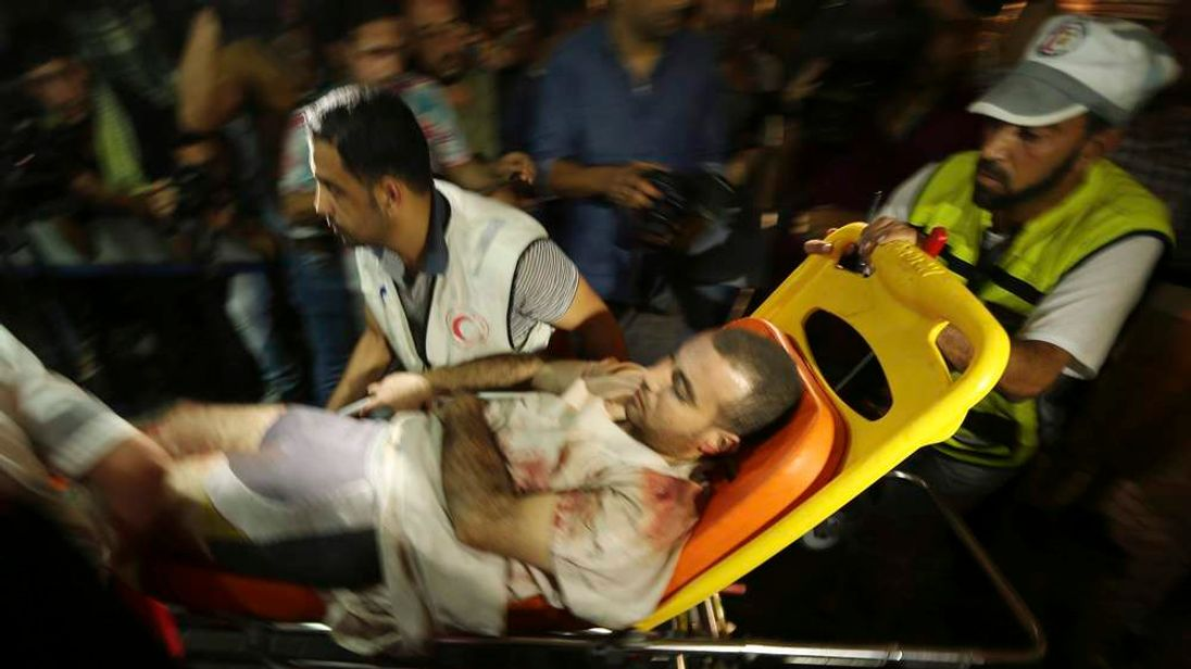 A wounded Palestinian, who hospital officials said was injured in an Israeli air strike, is wheeled into a hospital in Gaza City